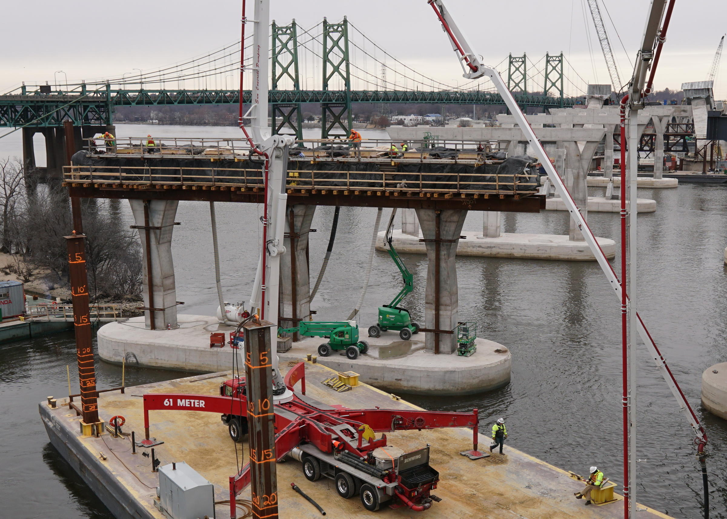WVIK, Quad Cities NPR reports another phase of the I-74 Bridge Project has been completed. The image shows crews finishing pouring concrete for all the piers located in the river.